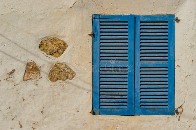 Oud blauw vensterblind met rustieke witte pleistermuur stock foto's