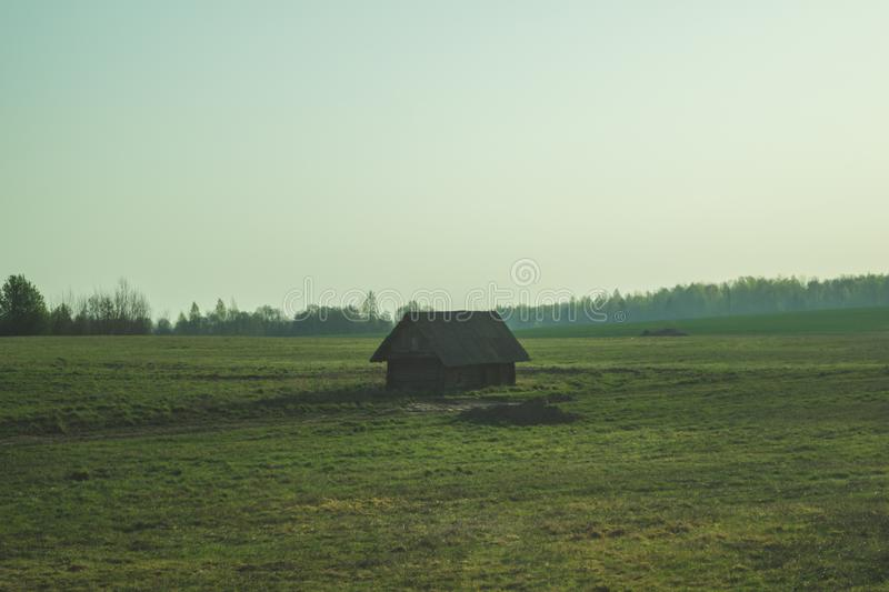Oud blokhuis in het platteland de huistribunes alleen op het gebied stock foto's