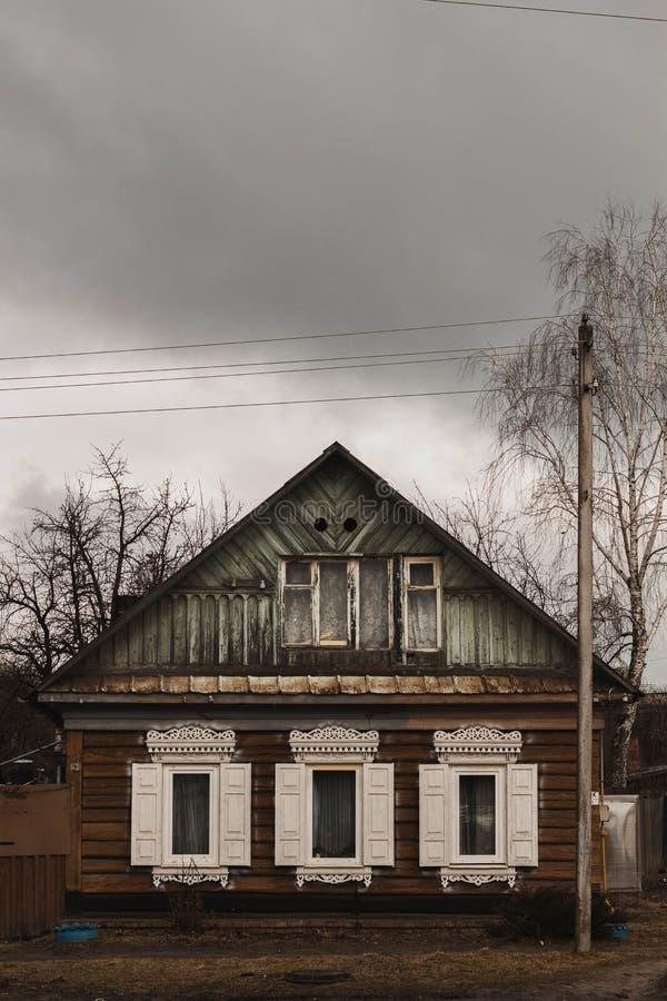 Oud blokhuis met witte blinden in bewolkt weer stock foto's