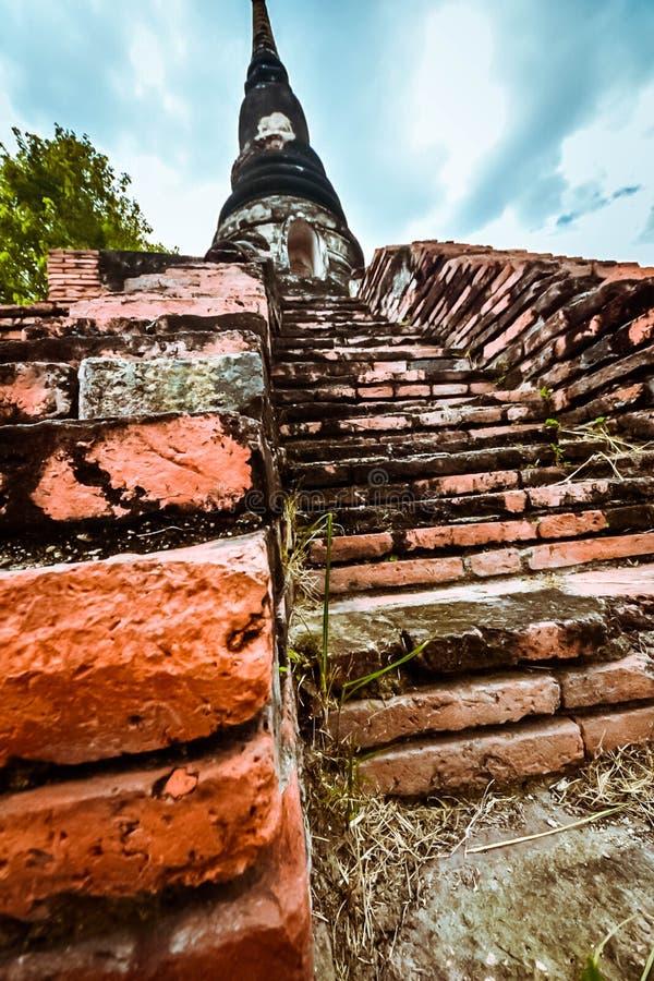 Oud boeddhistisch standbeeld op oude pagodeachtergrond stock foto