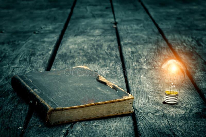 Oud boek aan flarden op een houten lijst Het lezen door kaarslicht Uitstekende samenstelling Oude bibliotheek stock afbeelding