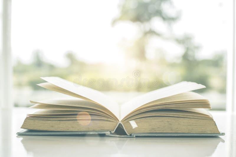 Oud boek die op vensterbank met aardachtergrond openen in ochtend stock afbeeldingen