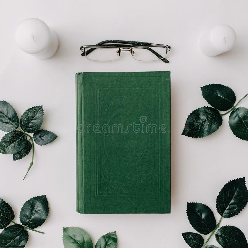 Oud boek, glazen, groene bladeren op witte achtergrond Vlak leg stock foto's