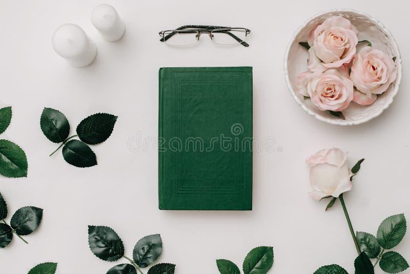 Oud boek, glazen, roze rozen op witte achtergrond Vlak leg stock foto