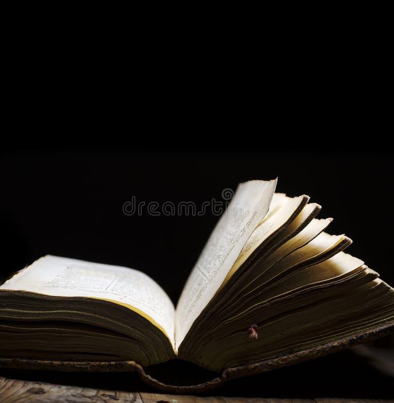 Oud boek open op uitstekende lijst aangaande donkere achtergrond Lees en bestudeer uitstekende bijbel met verlichte pagina Litera stock foto's