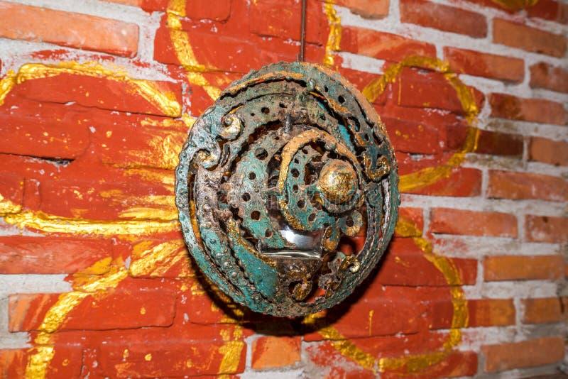 Oud bronsschild op de oranje bloembakstenen muur stock foto's