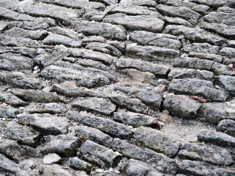 Oud cobblestoned bestratingsachtergrond stock afbeeldingen