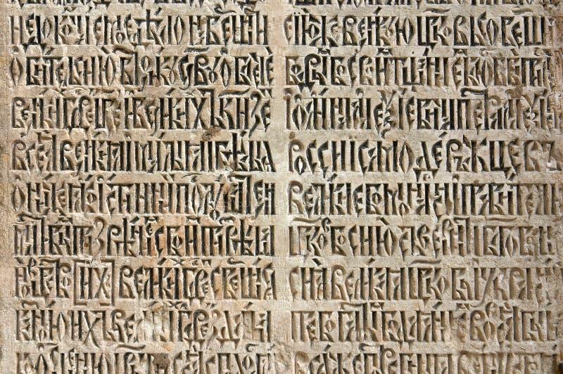 Oud - cyrillische inschrijving op een steen stock afbeelding