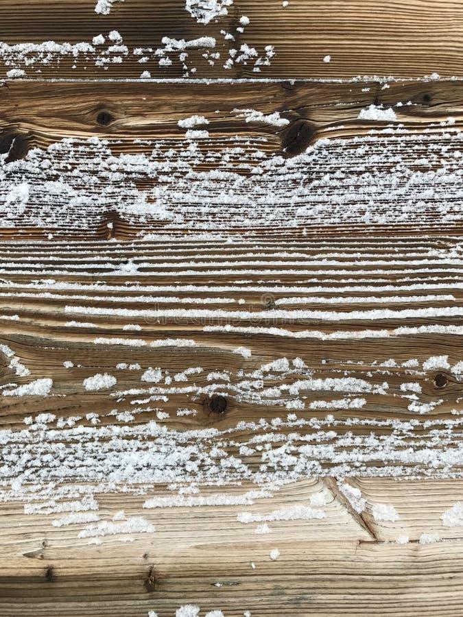 Oud die hout met sneeuwachtergrond wordt behandeld stock afbeeldingen