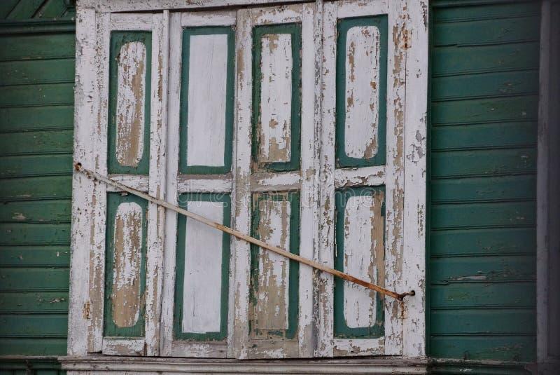 Oud die venster door witte houten blinden op de groene muur wordt gesloten stock foto's