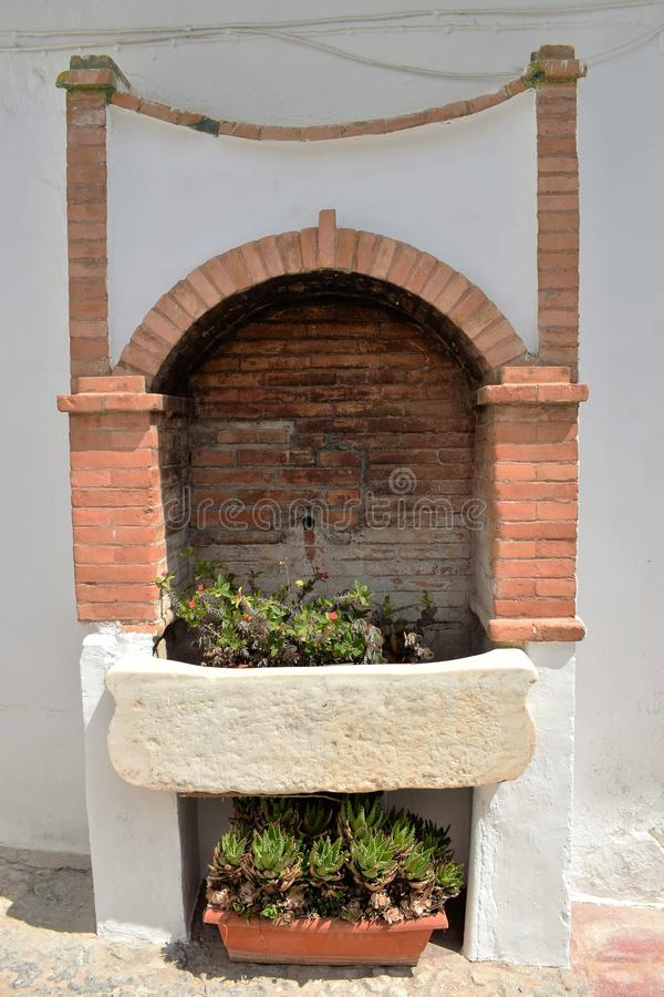 Oud die waterkraan en bassin als installatiepot wordt gebruikt in Frigiliana, Spaans wit dorp Andalusia royalty-vrije stock fotografie