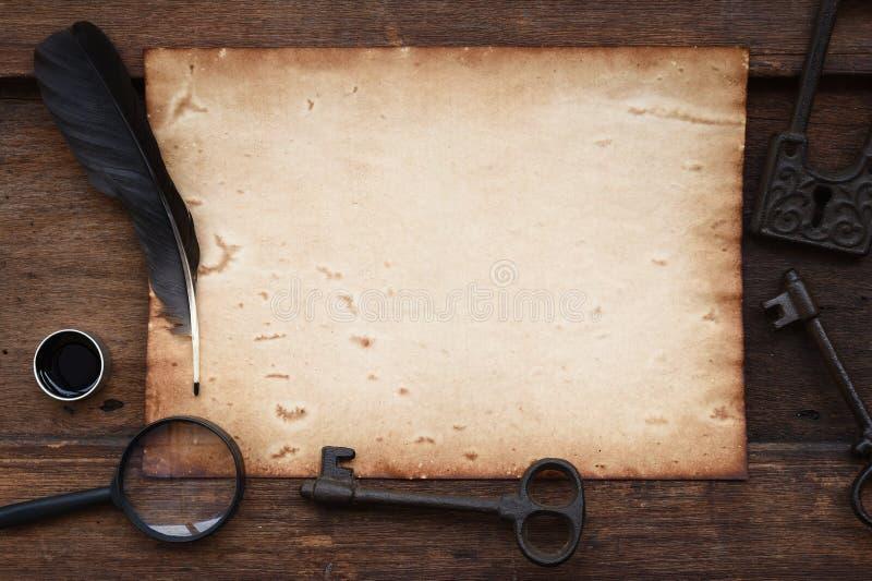 Oud document op bruine houten textuur met sleutel, veer en inkt, vergrootglas stock afbeeldingen