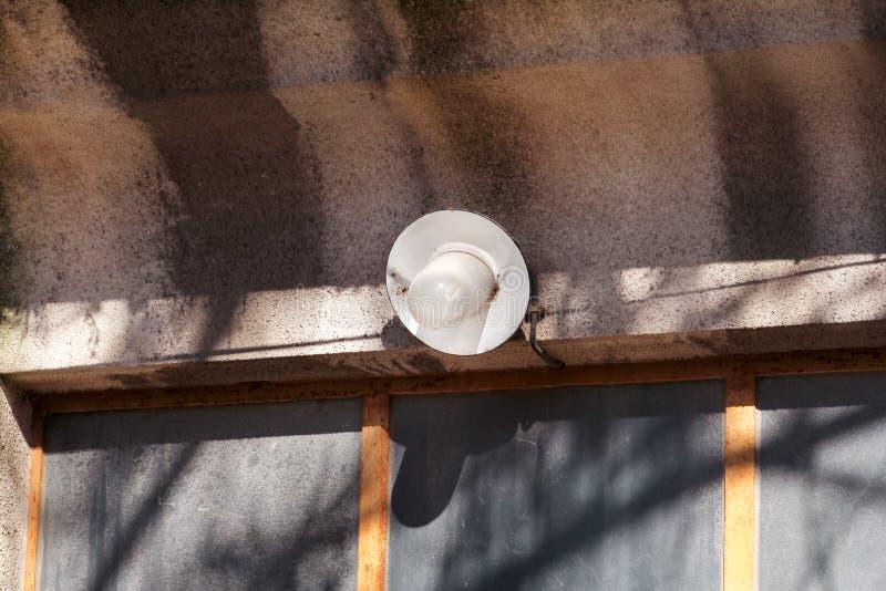 Oud een één enkele gloeilamp en lamp openlucht bij voormuurdeur van huis, close-up royalty-vrije stock foto's