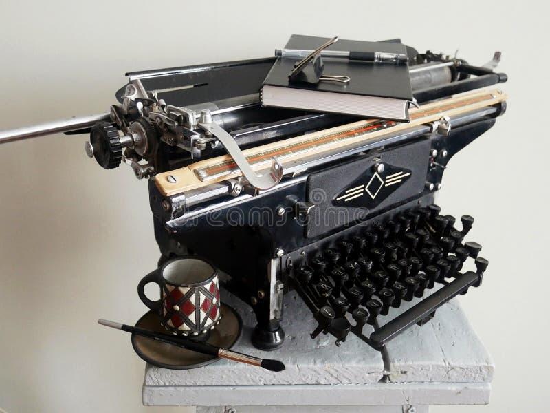 Oud een voorwerp-schrijfmachine en een zwarte kop stock foto's