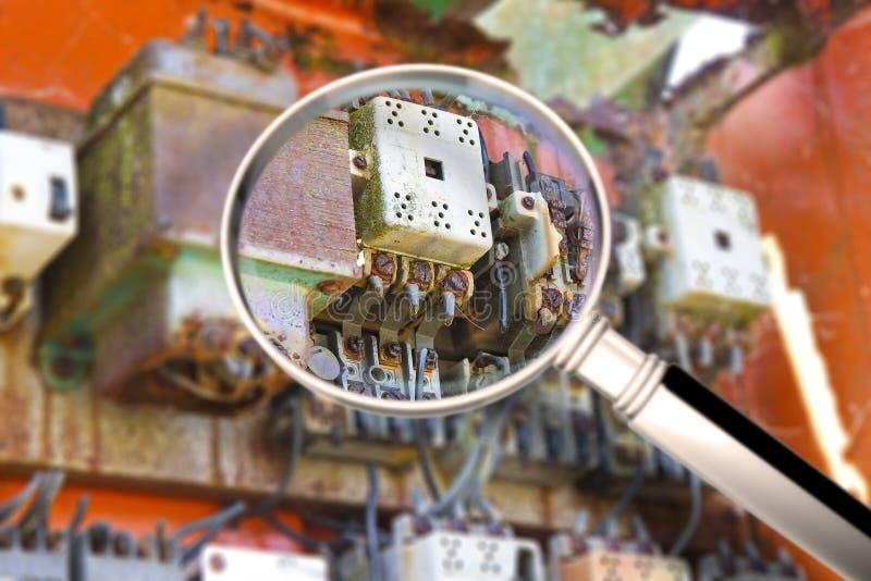 Oud elektrocontrolebord binnen een beschadigde die metaalkabeldoos - conceptenbeeld door een vergrootglas wordt gezien stock foto's