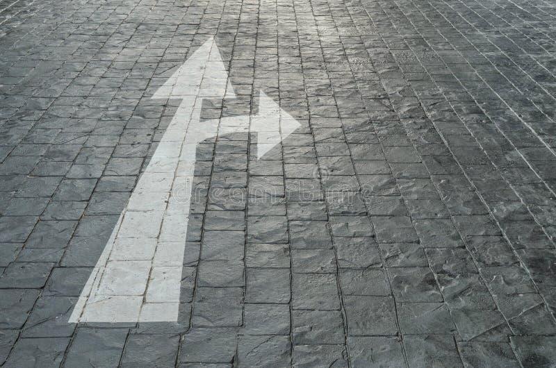 Oud en bleek wit geschilderd de pijlteken van de close-upoppervlakte in beweging voorwaarts of rechterkant op de zwarte vloer van stock afbeelding