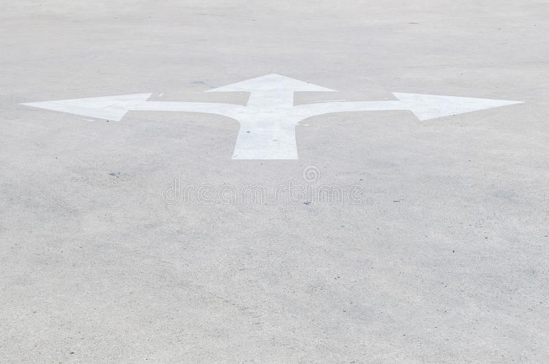 Oud en bleek wit geschilderd de pijlteken van de close-upoppervlakte op de vloer geweven achtergrond van de cementstraat met exem stock fotografie