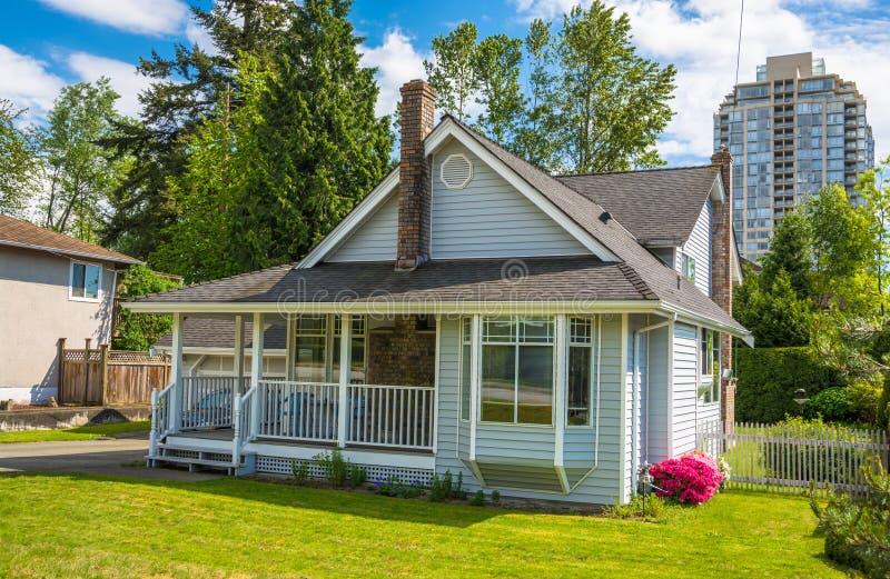 Oud familiehuis met klein terras en groen gazon van de vooryard op stedelijk gebied stock afbeeldingen