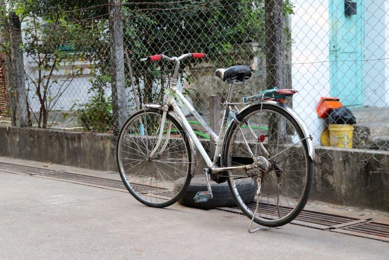Oud fietsparkeren op de straat naast de ijzeromheining stock fotografie