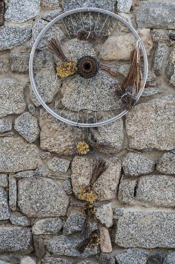 Oud fietswiel en droge die bloemen als decoratie op een stenenmuur wordt voorgesteld in Frankrijk royalty-vrije stock foto's