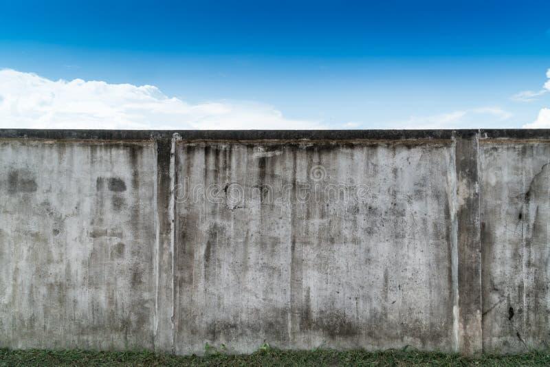 Oud gebarsten grijs cement of concrete muur met blauwe hemel als achtergrond Grunge gepleisterde gipspleister geweven achtergrond stock foto