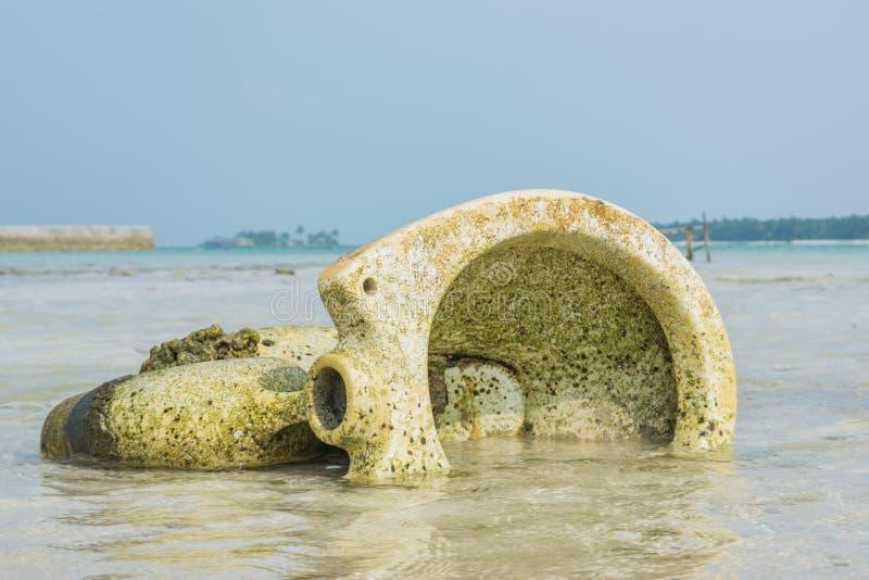 Oud gebroken toilet in de oceaan bij het tropische strand stock fotografie