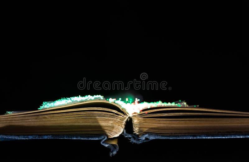 Oud, oud, geel geopend boek, gloeiende optische vezels royalty-vrije stock afbeelding