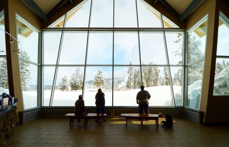 Oud Gelovig Bezoekercentrum binnen Niet identificeerbare bezoekers binnen het letten op Oude Gelovige Geiser Yellowstone Nationaa stock fotografie