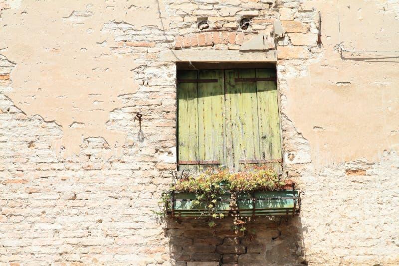 Oud gesloten venster in gebroken muur royalty-vrije stock afbeelding