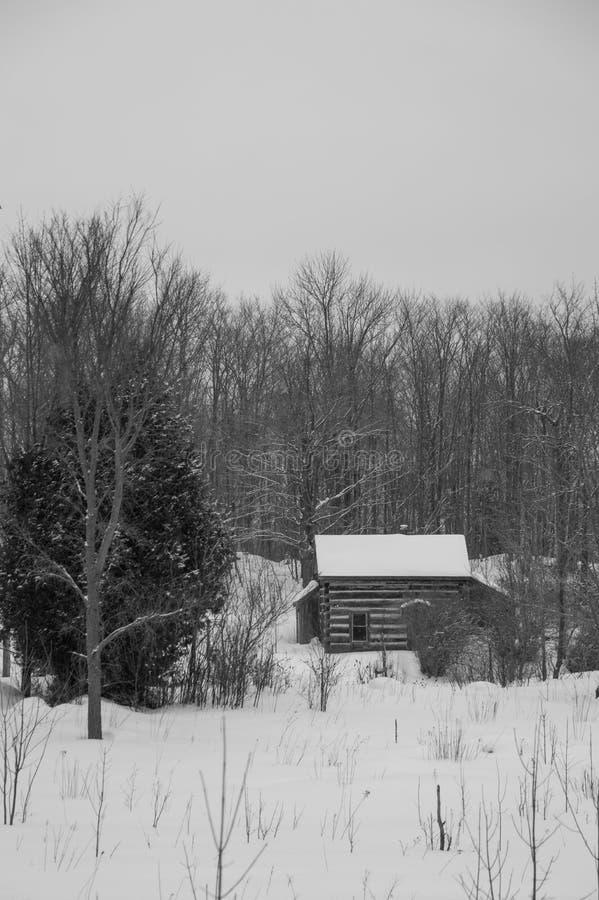 Oud gezaagd blokhuis in de sneeuw in bw van het de winterlandschap stock foto's