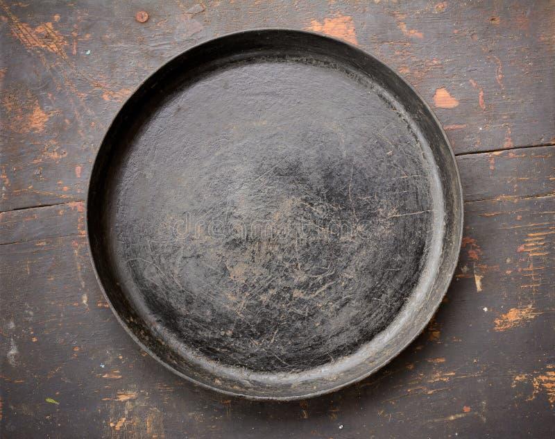 Oud Gietijzer die Pan On The Black Wooden-Lijstclose-up braden royalty-vrije stock foto