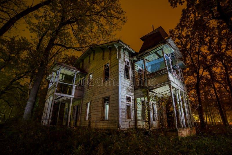 Oud griezelig houten verlaten achtervolgd herenhuis bij nacht stock afbeelding
