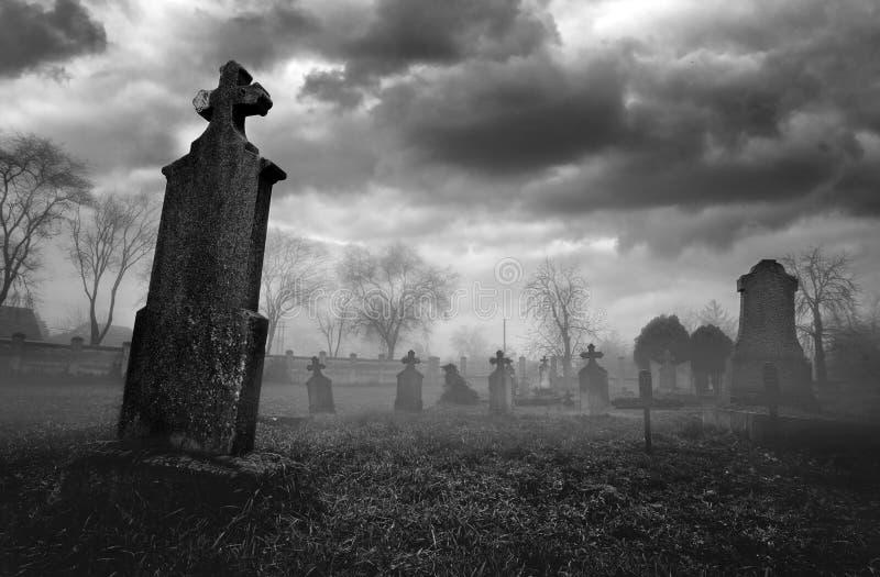 Oud griezelig kerkhof op stormachtige de winterdag in zwart-wit royalty-vrije stock foto