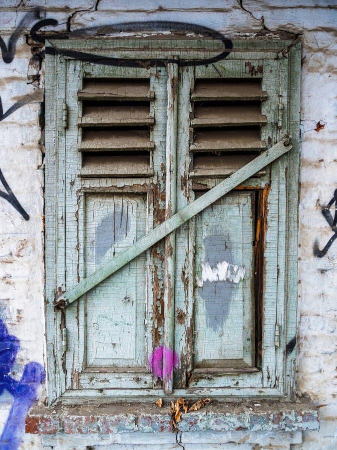 Oud grijs gesloten venster met blinden Geruïneerde muur van een oud huis royalty-vrije stock foto's