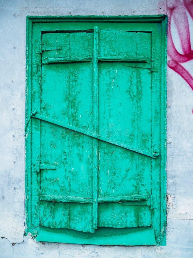 Oud groen gesloten venster met blinden Geruïneerde muur van een oud huis stock afbeelding