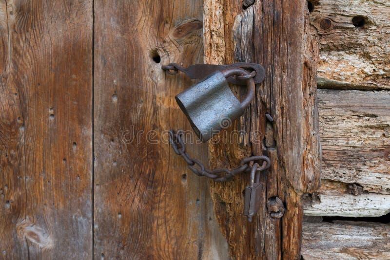 Oud hangslot op een houten deur Roestig graanschuurslot stock afbeelding