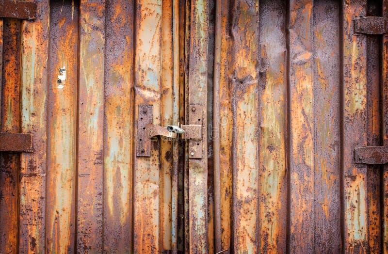 Oud hangslot op roestige garagekragen stock foto