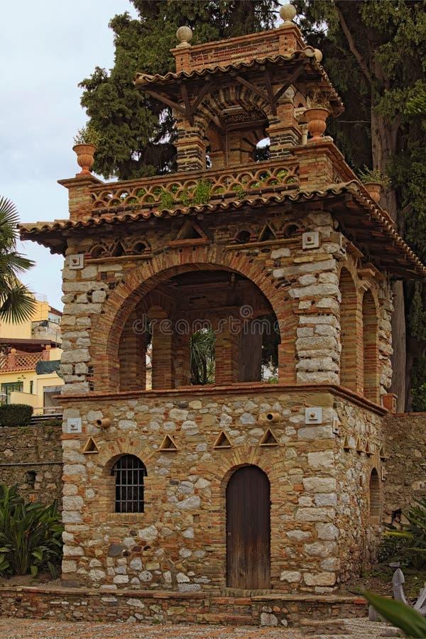 Oud herenhuis in Tuin van Villa Comunale in Taormina-stad Openbare tuin op Sicilië, Italië De oude bouw met buitenkant royalty-vrije stock foto's