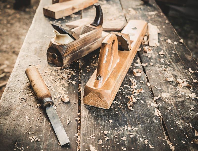 Oud houtbewerkingswerktuig: houten vliegtuig, beitel en tekeningsmes in een timmerwerkworkshop over vuile rustieke behandelde lij royalty-vrije stock afbeelding