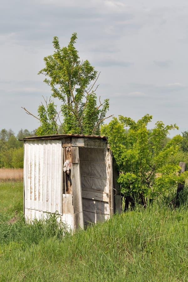 Oud houten dilapidated toilet in een dorp onder de bomen stock afbeelding