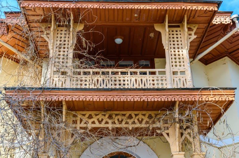 Oud houten gesneden die balkon met oude dicht omhoog klimop wordt overwoekerd stock foto's