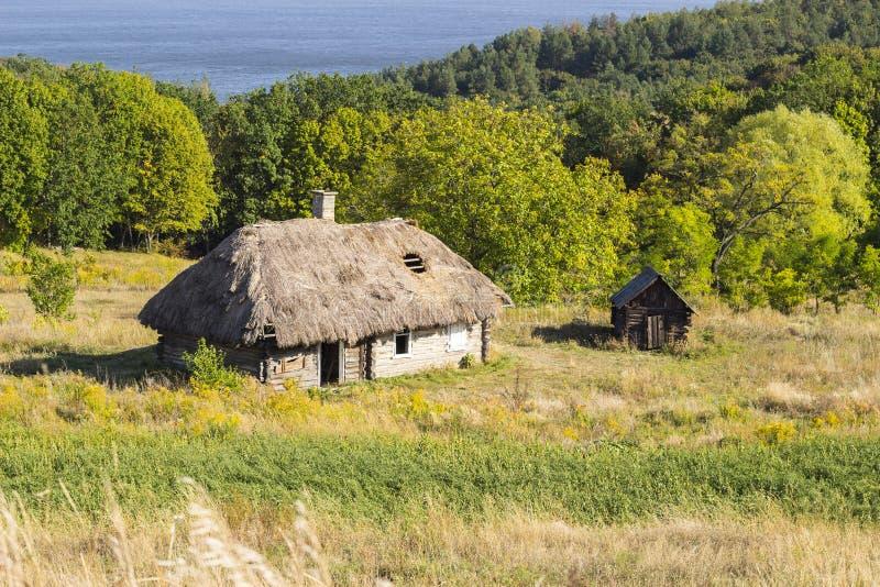Oud houten huis met met stro bedekt dak in de zomer Zonnige dag, de oude bouw stock afbeelding