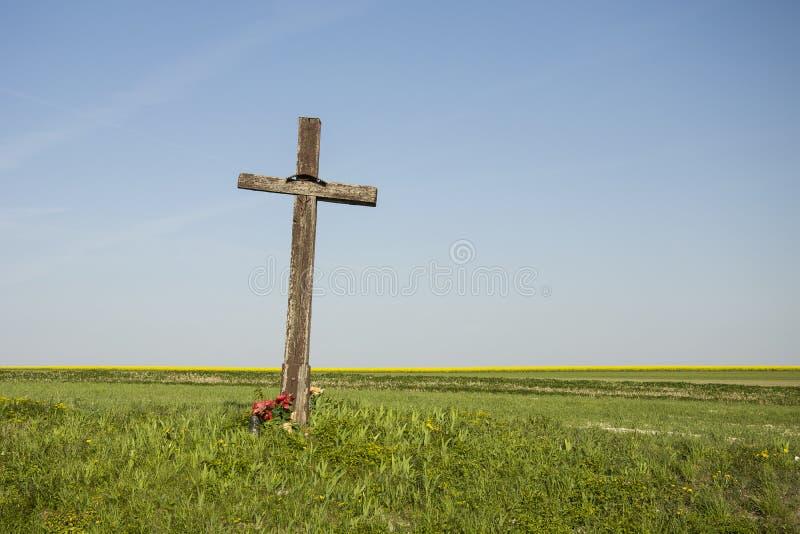 Oud houten kruis op het gebied stock afbeelding