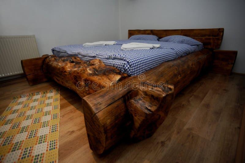 Oud houten rustiek bed met blauwe bladen in het plattelandshuisje stock foto