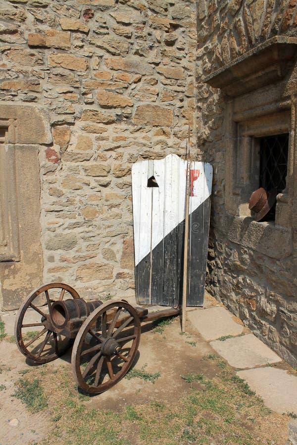 Oud houten schild, spear en kanon bij de muren van een middeleeuws kasteel royalty-vrije stock afbeeldingen