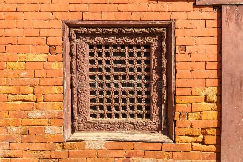 Oud houten traditioneel Nepalees venster in bakstenen muur nepal stock afbeelding