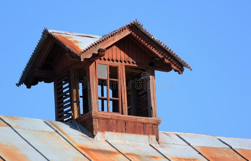 Oud houten zoldervenster op het dak stock foto's