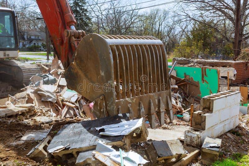 oud huis die door grote backhoe worden vernietigd stock foto's