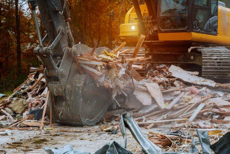 oud huis die door grote backhoe worden vernietigd stock afbeelding