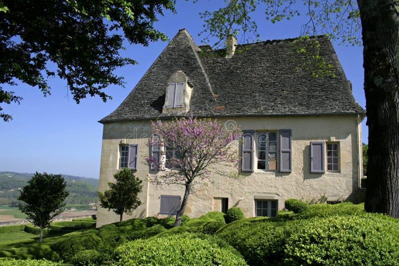 Oud huis in gemodelleerde tuin stock foto's